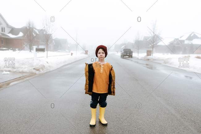 Somber boy standing alone in the foggy road