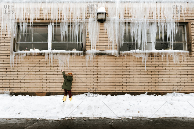 Little kid reaching for long icicles hanging from windowsill