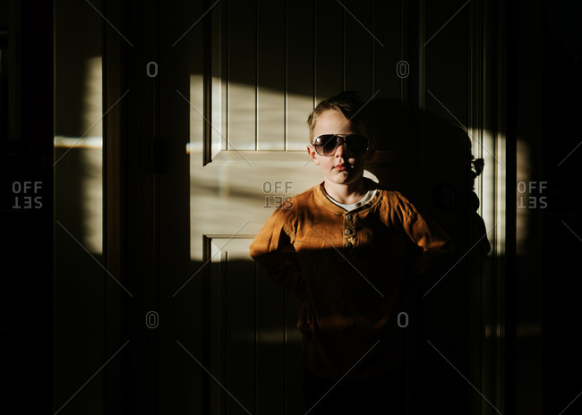Cool kid in shades standing with back to doorway in dark room