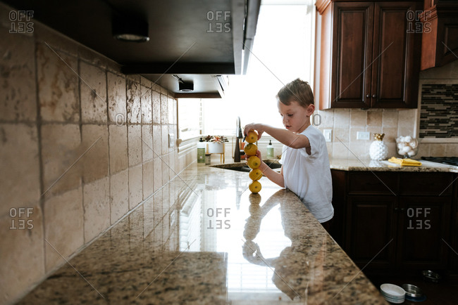 Boy stacking lemons on top of each other in kitchen