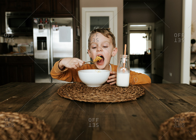 Hungry kid about to eat a big spoonful of macaroni and cheese at dining room table
