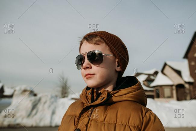 Boy staring at sun through aviator sunglasses on snowy day
