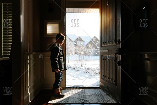 Hesitant boy stalling by open doorway