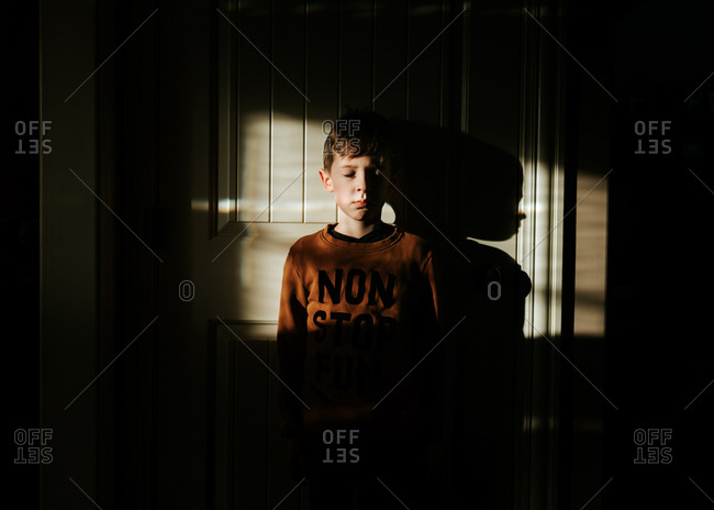 Pouting boy standing alone with back to wall in darkness
