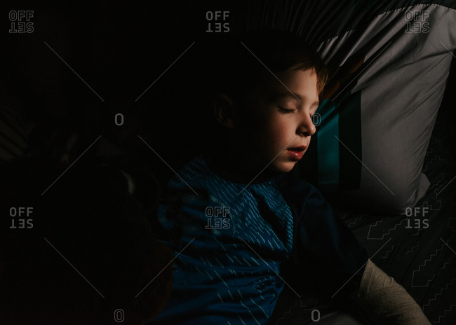 Young boy taking a nap in dark room