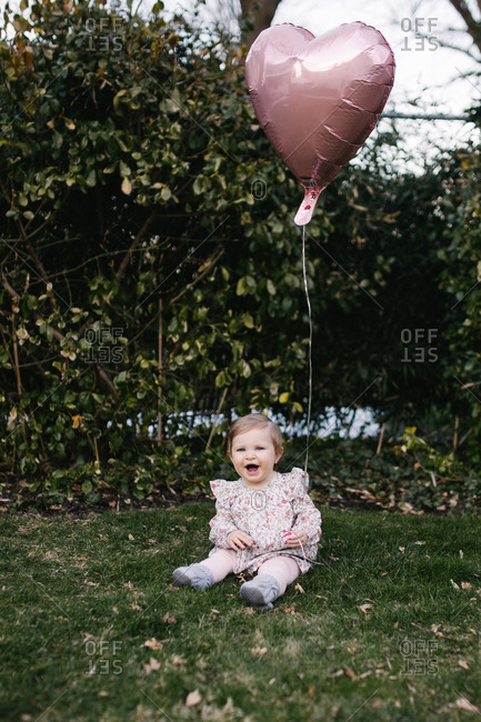 Outdoor baby birthday portrait with heart baloon