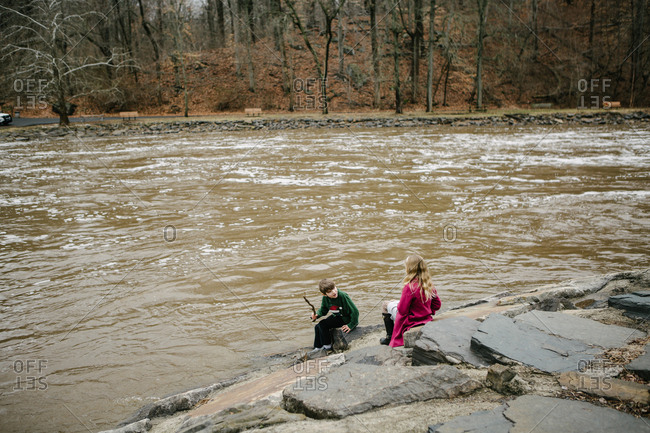 Kids playing on rocky river bank on overcast day