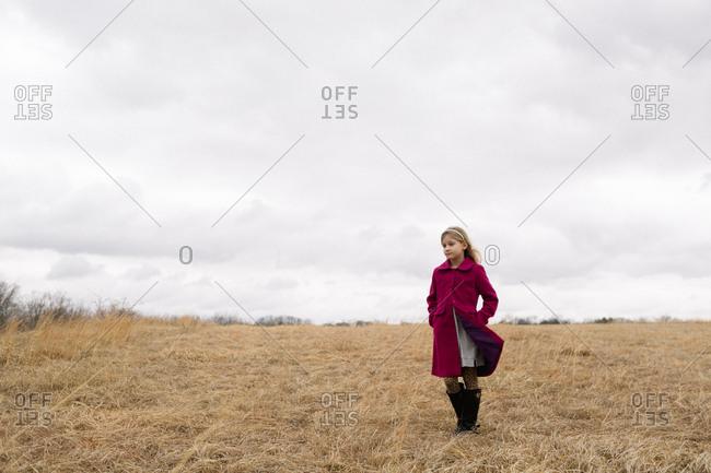 Blonde girl standing in open field alone