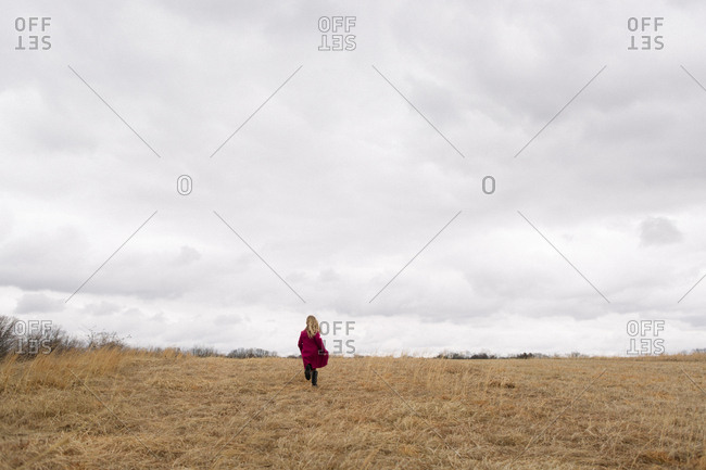 Girl running across empty meadow on cloudy day