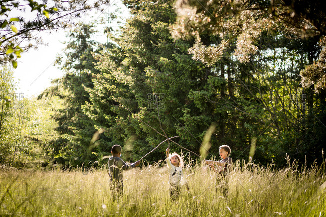 Kids playing with sticks in a field