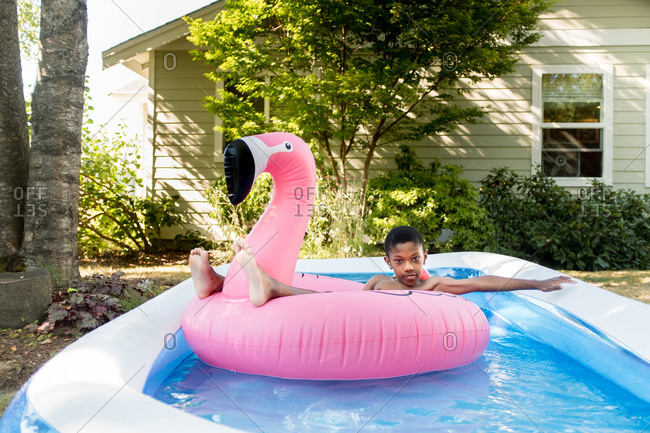 Boy lounging in a pink flamingo floaty in a backyard pool