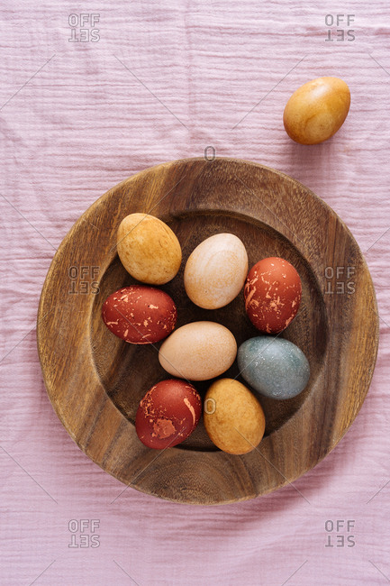 Easter eggs naturally dyed with vegetable and fruit on a wooden plate