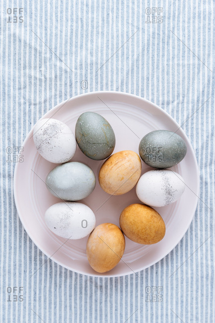 Naturally dyed Easter eggs on a dish on a blue striped cloth