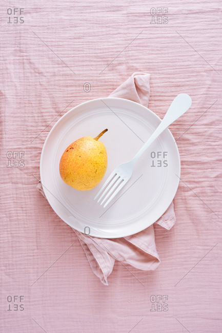 Yellow pear on a white dish on pink background