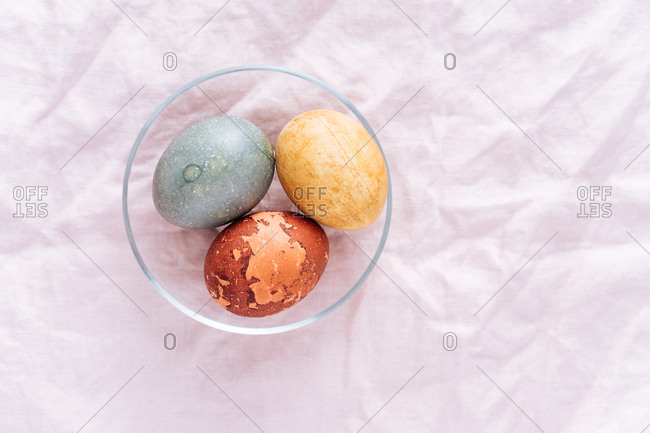 Easter eggs naturally dyed in a glass dish