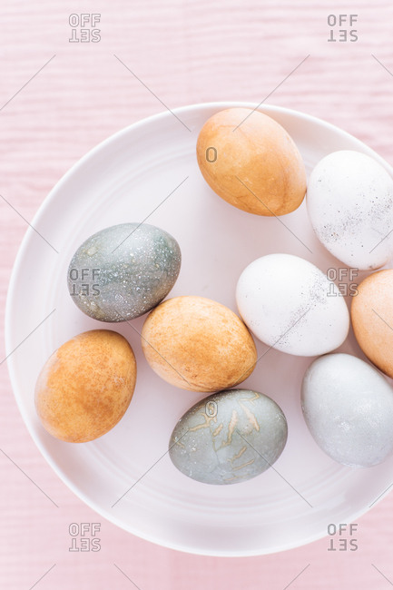 Overhead view of naturally dyed Easter eggs on a plate