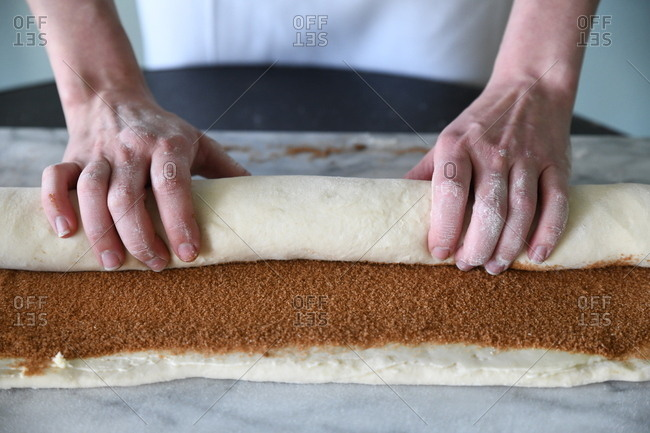 Hands rolling up a cinnamon roll