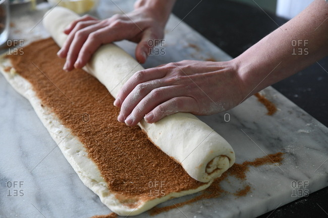 Baker rolling up a cinnamon roll