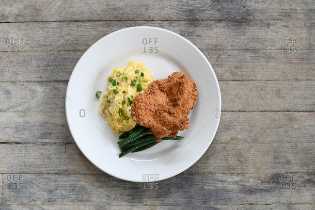 Fried chicken with mashed potatoes and green beans on a rustic table