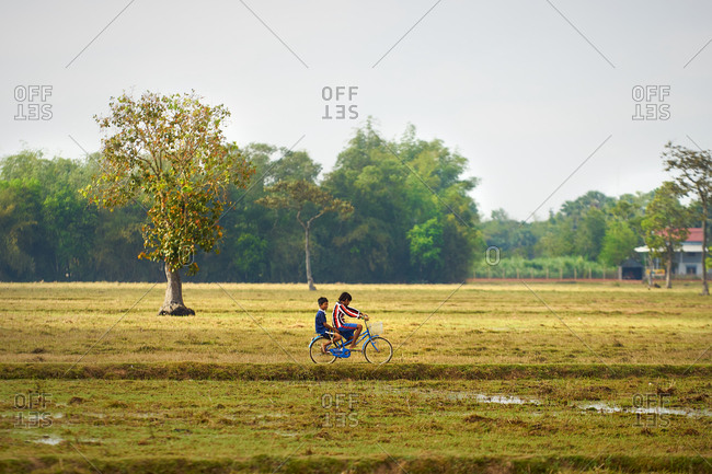 Cambodia - March 30, 2017: Two boys riding a bicycle in rural field