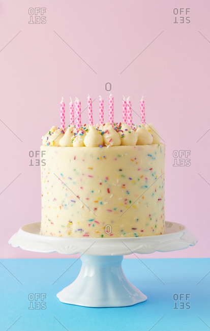 Confetti birthday cake on blue and pink background with birthday candles