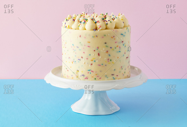 Confetti birthday cake on blue and pink background stock photo - OFFSET