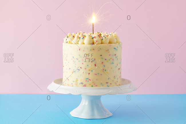 Confetti birthday cake on blue and pink background with sparkler