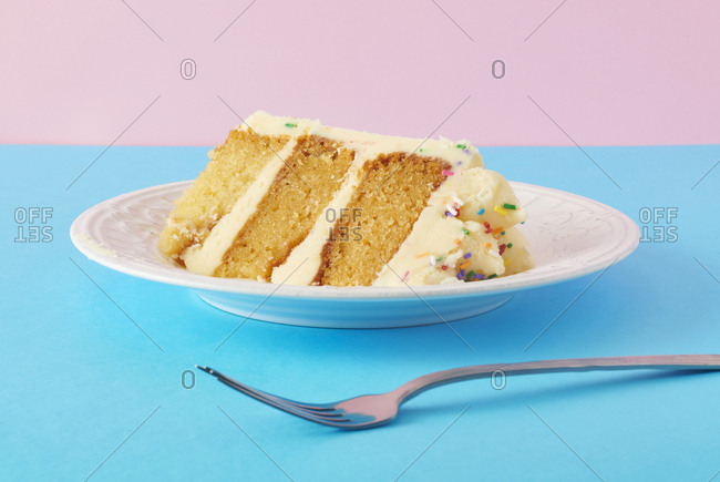 Slice of confetti birthday cake on blue and pink background