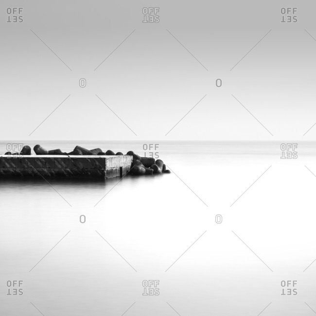 Black and white long exposure of pier at sea in Atami, Shizuoka Prefecture, Japan