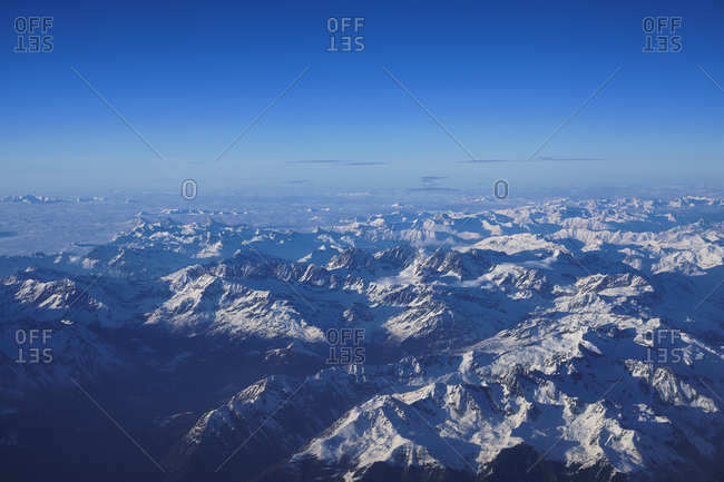 Bird's eye view of mountainscape covered in snow from an airplane