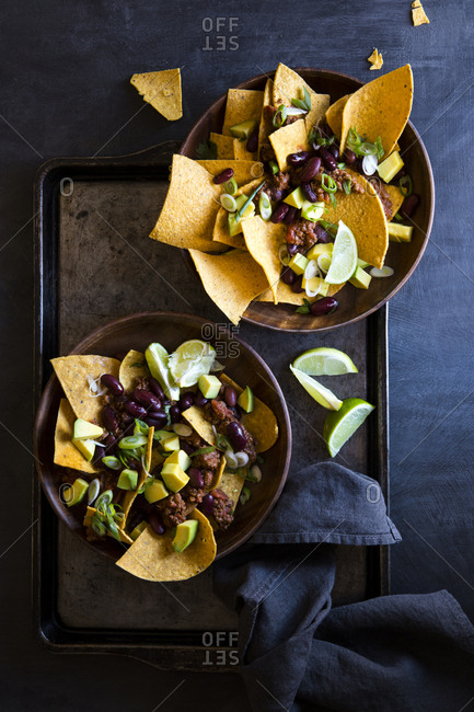 Nachos with beef, scallions, black beans and lime in bowls