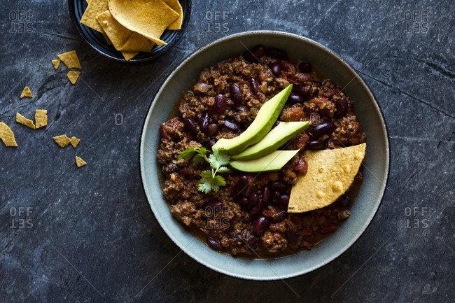 Beef and black bean chili with avocado, sour cream and tortilla chips