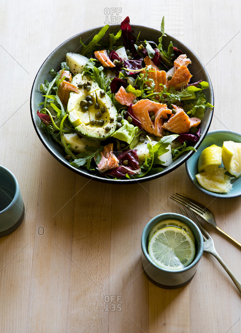 Salmon and avocado with leafy greens in a bowl