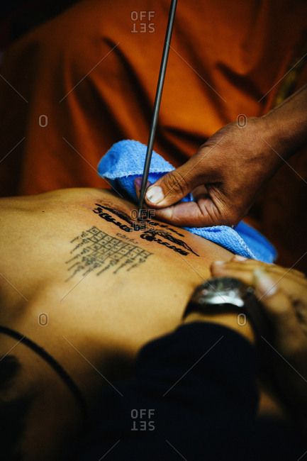 "March 19, 2011: Close-up shot of monk making ""sak yant"" traditional hand poked magic tattoo during Wai Khru festival in Wat Bang Phra, Thailand"