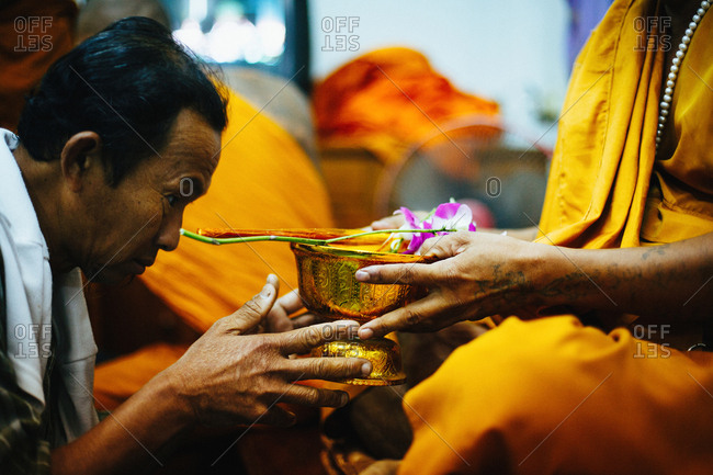 "March 19, 2011: Old Thai man making offering to monk who making ""sak yant"" traditional hand poked magic tattoo during Wai Khru festival in Wat Bang Phra, Thailand"
