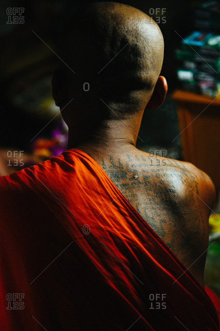 "March 19, 2011: Close-up back shot of monk making ""sak yant"" traditional hand poked magic tattoo during Wai Khru festival in Wat Bang Phra, Thailand"