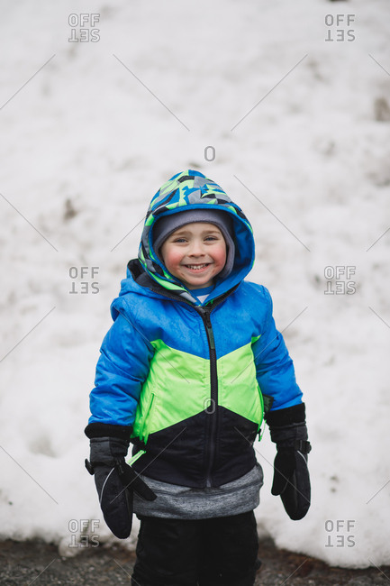 Little boy all bundled up and happy to be out in the snow