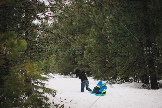 Parent trudging through the snow dragging kids in sled