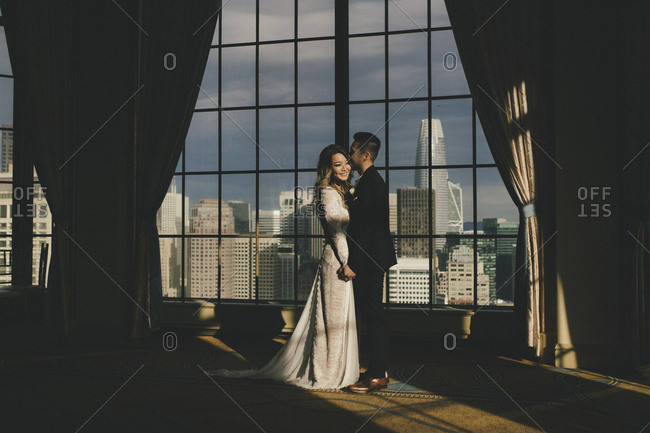 Portrait of bride and groom standing together by window with cityscape backdrop