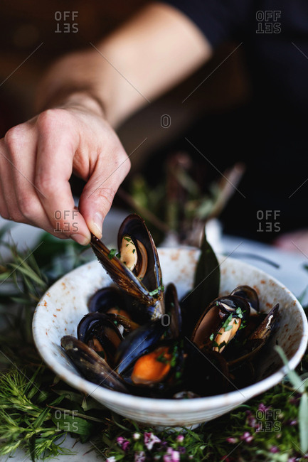 Close up of hand picking mussel from bowl