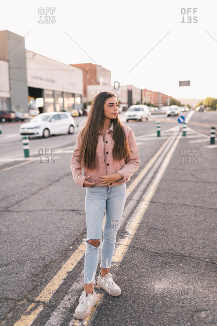 Portrait of young Latina girl standing on the street at sunset