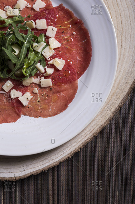 Overhead view of Carpaccio with parmesan cheese and arugula seasoned with oil and pepper