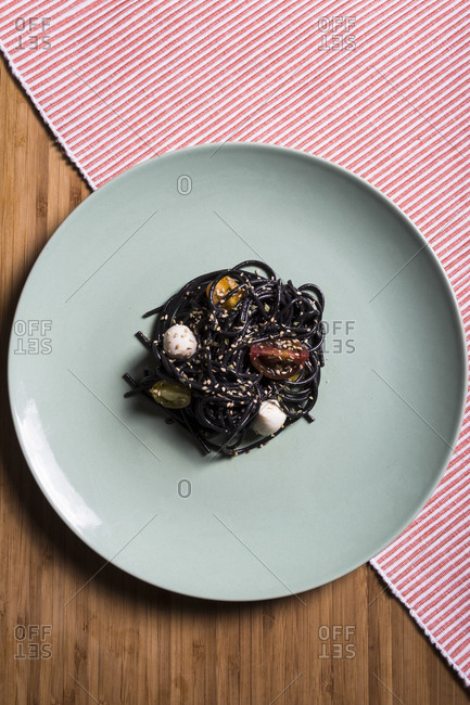 Overhead view of squid ink spaghetti with mozzarella and cherry tomatoes, sesame seeds seasoned with garlic and oil