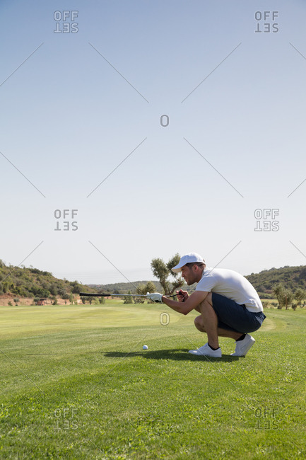 Golf player measuring stroke angle with golf club