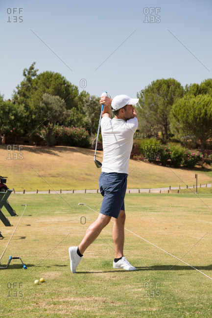 Young golf player practicing on golf driving range