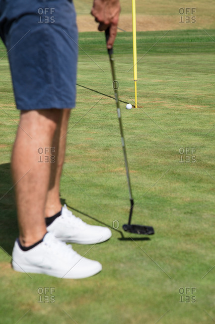 Golfer playing golf ball in the hole