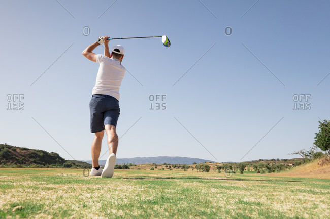 Professional golfer looking at ball after the swing