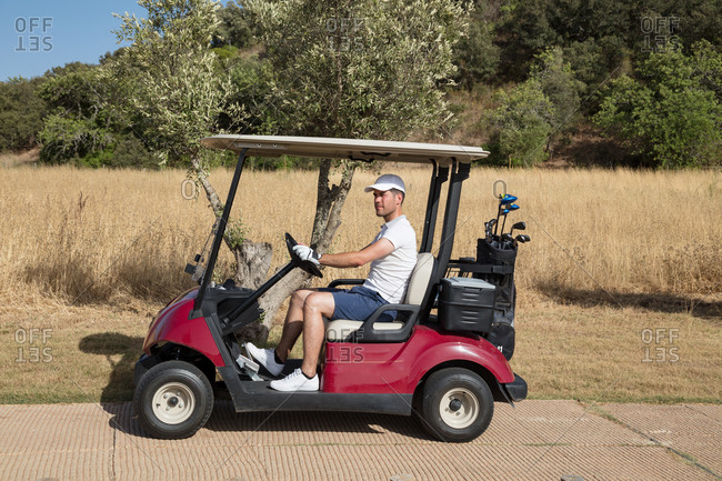 Man driving golf cart in nature