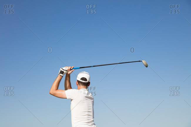 Golf: Male golfer after swing against blue sky