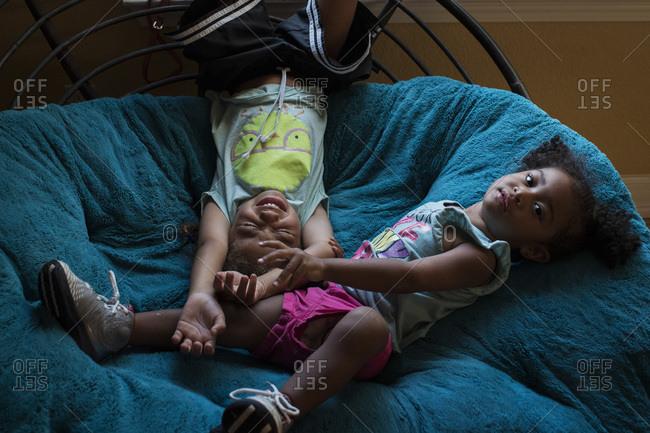 Brother and sister playing on papasan cushion